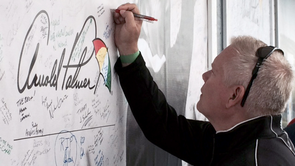 A Ryder Cup spectator writes a message to Arnold Palmer on the massive posters outside of the merchandise tent.