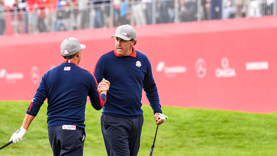 Phil Mickelson and Rickie Fowler of Team USA celebrate after Fowler holed out from off the ninth hole green to go 1-up during morning Foursome Matches of the 2016 Ryder Cup at Hazeltine National Golf Club.