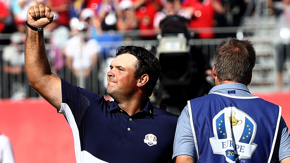 Patrick Reed of the United States celebrates on the 18th green after winning his match as Rory McIlroy of Europe looks on during singles matches of the 2016 Ryder Cup at Hazeltine National Golf Club.