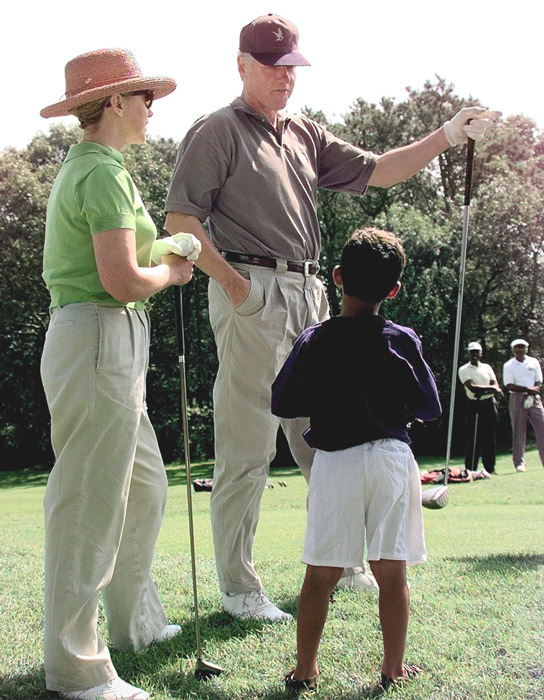 President Bill Clinton (C) and First Lady Hillary Rodham Clinton (L) talk with Mercer Cook (R), age 5, at Mink Meadows Golf Course on Martha's Vineyard.