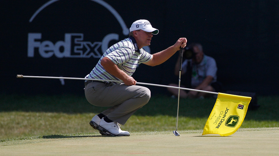 Steve Stricker holds a flagstick off the ground during the John Deere Classic.