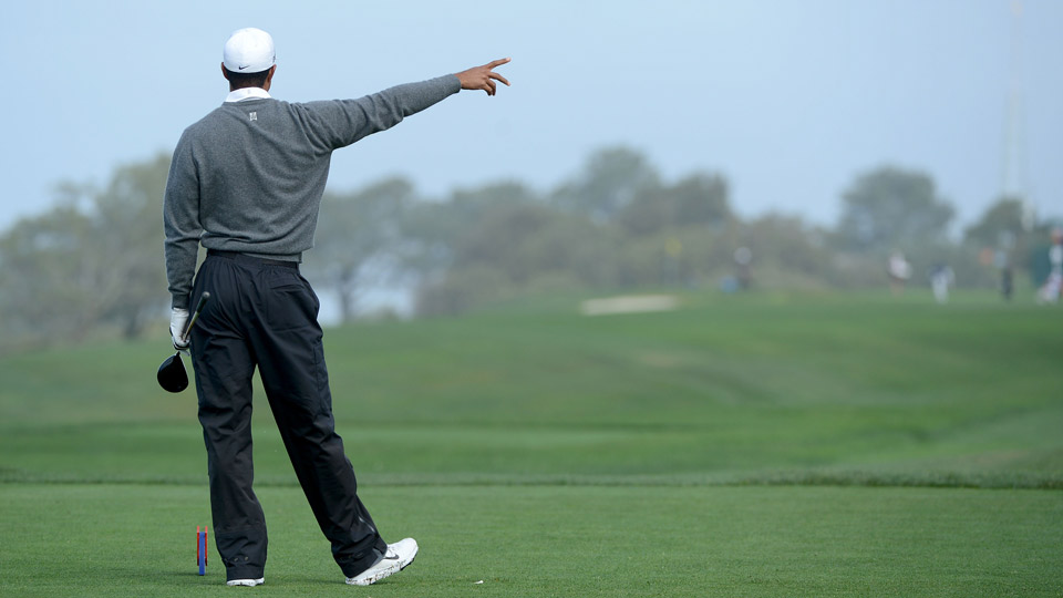 Tiger Woods points right after a wild tee shot.