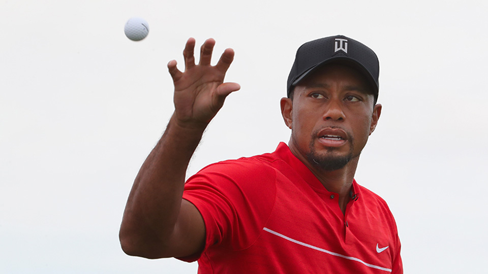 Tiger Woods catches a golf ball on the practice range.
