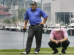 Angel Cabrera, left, sizes up a putt on the 6th hole Friday at the Singapore Open as Ernie Els was on his way to shooting a disappointing 5-over 76.