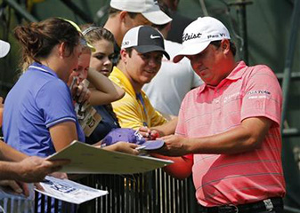 Jason Dufner signs autographs on the eighth hole at Valhalla Golf Club during a practice round prior to the start of the PGA Championship.