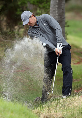 Jordan Spieth blasts out of a creek on the sixth hole at the Monterey Peninsula course. He bogied the hole, but finished the day tied for the lead at -9.