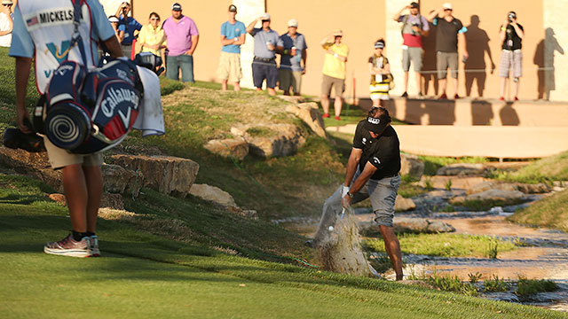 With one foot in the creek, Mickelson chipped onto the 18th green and birdied the hole to make the cut on the number.