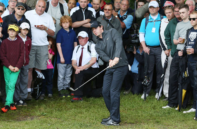 Rory McIlroy plays out of the rough at the fifth green during the first round at Wentworth.