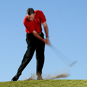 "You'll never compress the ball if you rise up on your downswing. Make your first move from the top a ""power lean."""