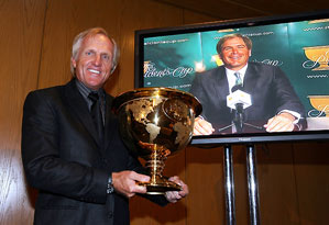 Greg Norman posed with the President's Cup trophy Tuesday as Fred Couples looked on via satellite from California.