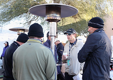Caddies huddle beneath a heat lamp during the frost delay Friday morning in Phoenix.