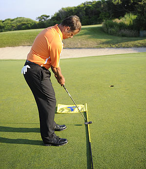 Swing your putter slightly to the inside of the flagstick going back and straight down the pole on your way through the ball to stop your tendency to pull the ball left.