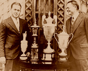 Robert T. Jones Jr. (Bobby Jones) and O.B. Keeler (left to right) are seen here with Jones' 1930 grand slam trophies: the British Open, the U.S. Amateur, the British Amateur and the U.S. Open.