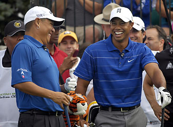 Stanford friends Notah Begay and Tiger Woods share a laugh before the start of the Notah Begay III Foundation Challenge at Atunyote Golf Club in Verona, N.Y., on Aug. 24, 2009