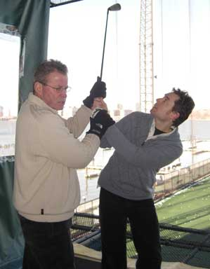 Christopher Shade learning more about the swing from John Hobbins at Chelsea Piers Golf Academy.