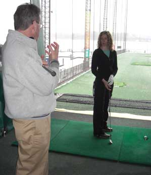 John Hobbins describing a swing's shoulder rotation to Paige Sellers at Chelsea Piers Golf Academy.