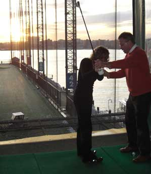 John Hobbins and Paige Sellers during a golf lesson at Chelsea Piers Golf Academy.