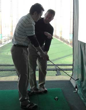 John Hobbins at Chelsea Piers Golf Academy helping Christopher address the ball.