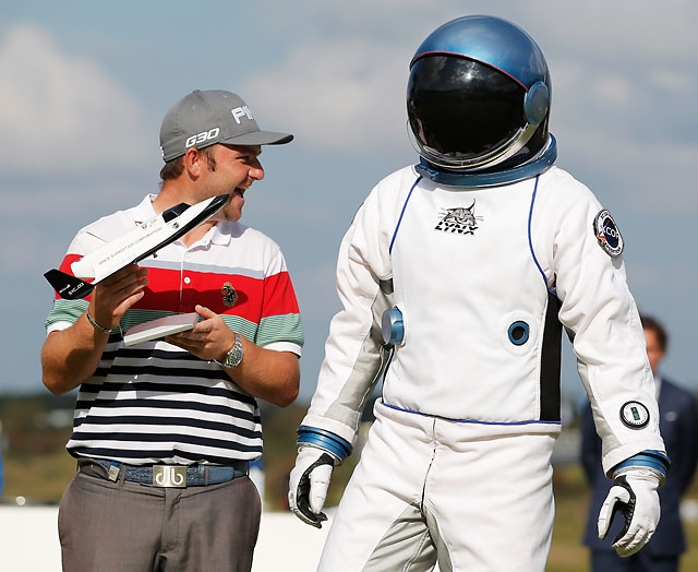 Andy Sullivan of England poses with his trophy and an astronaut from the XCOR spaceship after the final round of the KLM Open on Sunday.