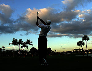 Tiger Woods drives from the 4th tee as dawn breaks during the final practice for the CA World Golf Championships.