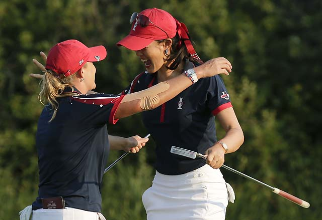 Michelle Wie celebrates with her playing partner, Cristie Kerr, after winning their four-ball match Friday.