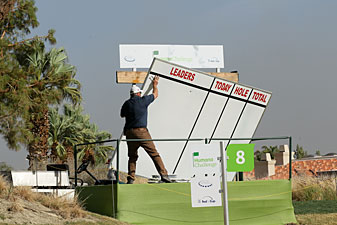 A course worker holds on to a scoreboard after high winds at the Nicklaus Private Course at PGA West.