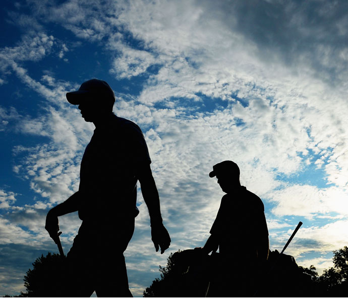 Tiger Woods walks with caddie Joe LaCava during a practice round prior to the start of the 95th PGA Championship at Oak Hill Country Club.