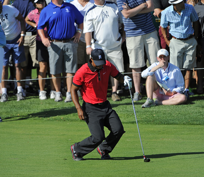 August 25, 2013: Woods falls to the ground in pain after hitting his second shot on the 13th hole during the final round of The Barclays at Liberty National Golf Club. He complained of back problems due to a hotel bed, but still tied for second at the tournament.
