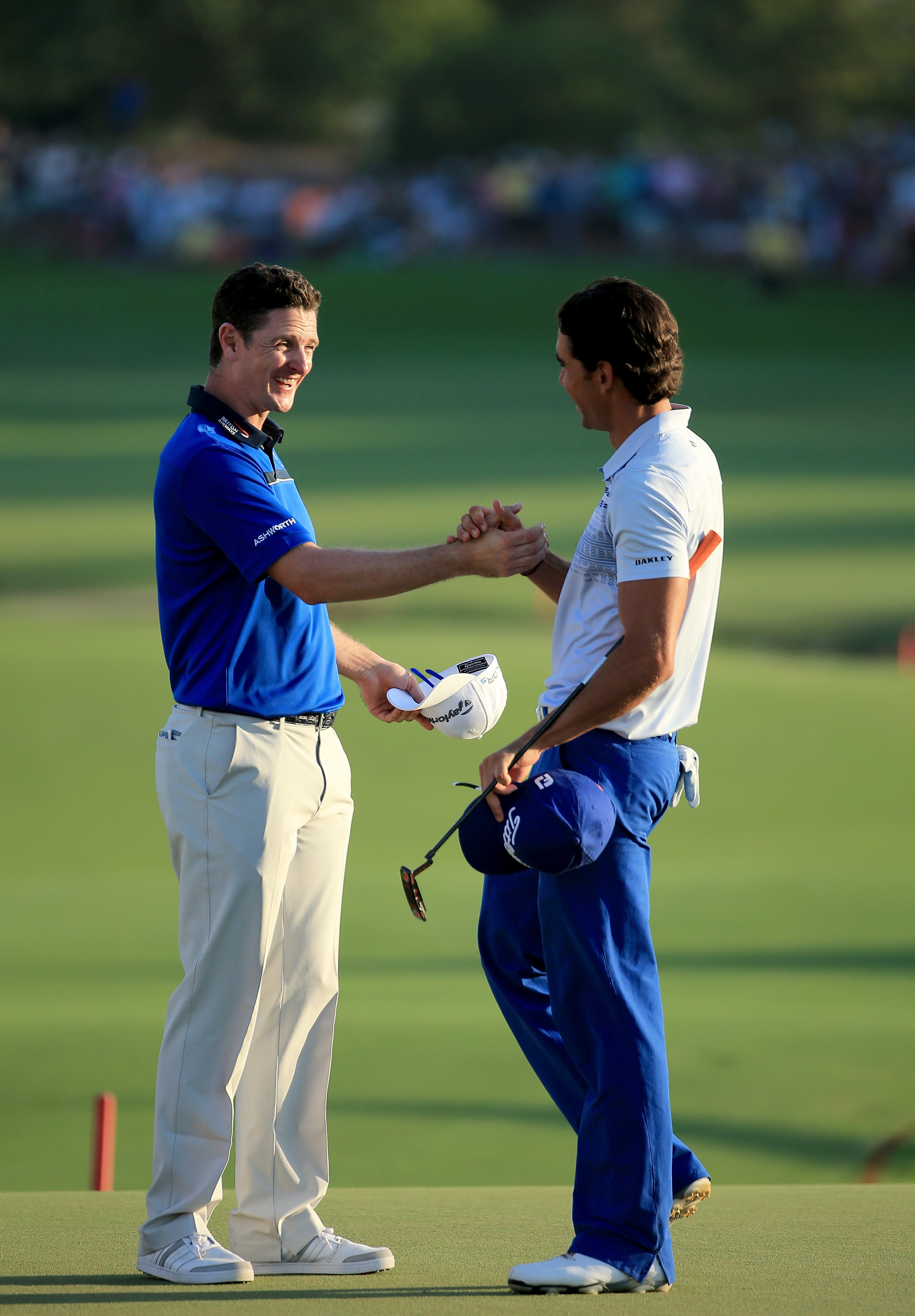 Rafa Cabrera-Bello of Spain (R) and Justin Rose of England shake hands after they had both made birdie at the par 5, 18th hole. Justin Rose sits third, shooting a third-round 68.