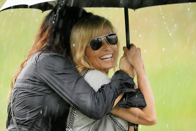 Amy Mickelson, Phil Mickelson's wife, waits under an umbrella during a weather-delay during the 2013 Presidents Cup at the Muirfield Village Golf Club.