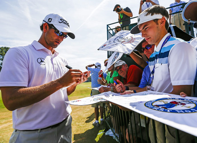 Adam Scott signs autographs after completing his practice round.