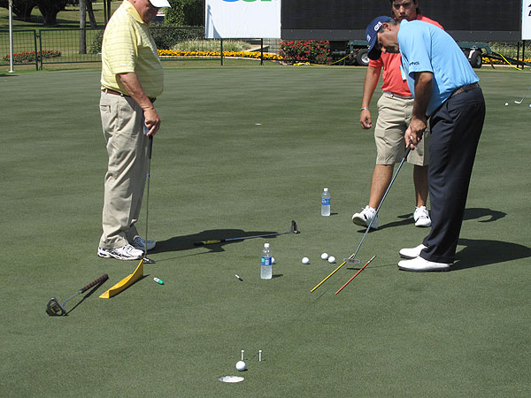 did not have his chalk line handy, so to practice his putting along a perfectly straight line he used a marker and a shaft. The tees are positioned to give the ball just 1/4-inch of clearance.
