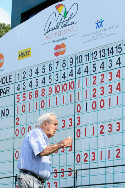 Arnold Palmer walks past the leaderboard on the 16th tee.