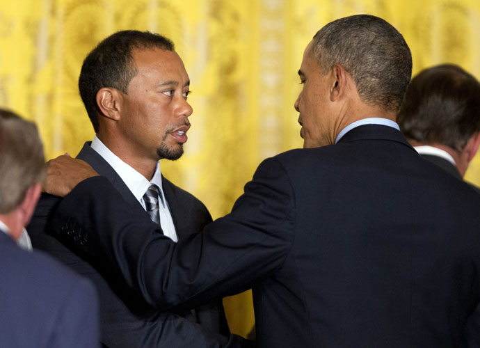 "President Barack Obama talks to Tiger Woods on Tuesday during a ceremony at the White House honoring the 2013 U.S. Presidents Cup team.  ""I'm not used to seeing these guys in suits,"" the President joked."