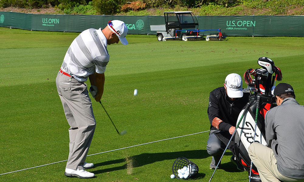 As part of his warm-up routine, Ben Crane hit a series of shots that bounced once, then landed in the ball collection hoppers attached to a range cart.