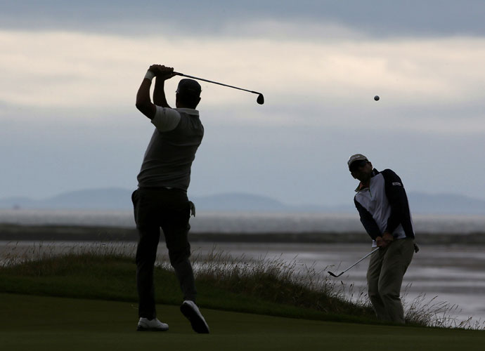 Fredrik Jacobson practices his swing while Ben Curtis chips onto the 13th green.