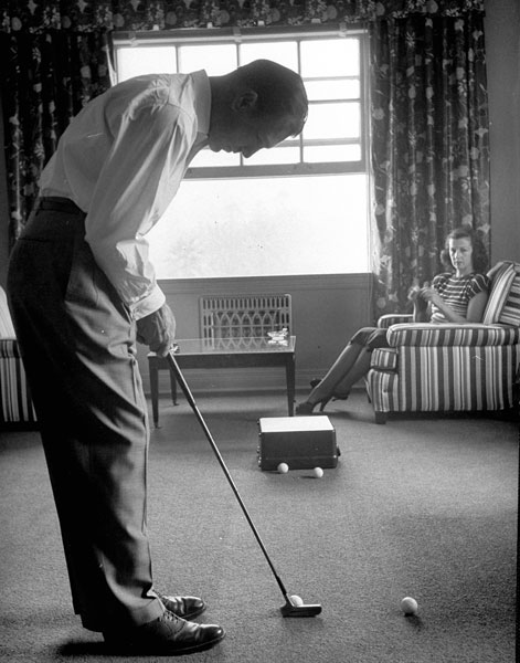 Ben Hogan gets in some hotel putting practice under the watchful eye of his wife, Valerie, at Town House in Los Angeles in October 1948.