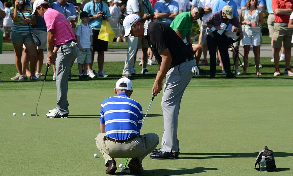 Bo Van Pelt practiced his putting on a training aid that resembles a green yardstick while his coach, former GOLF Magazine Top 100 Teacher Mark Wood, grabbed the balls as they dropped into the hole.