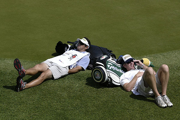 """Play was suspended during the fourth round of the Verizon Heritage at Harbour Town due to extremely high winds, so I walked around looking for images that showed the damage. As I walked to the clubhouse, I found two caddies — Mark Miller and Michael Bestor — relaxing on the edge of the practice green. You would think they were out tanning."""