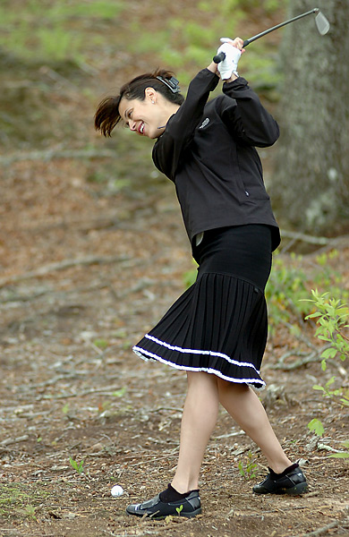 "Actress Catherine Bell laughs as she takes a ""practice swing"" while attempting to hit from the woods onto the 13th fairway during the third round of the BMW Charity Pro-Am at The Cliffs at Walnut Cove in 2006."