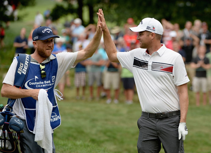 Chris Kirk high fives his caddie after making birdie on the 17th hole. Kirk kept the pace with McIlroy, matching his bogey-free 64 to get to 10 under.
