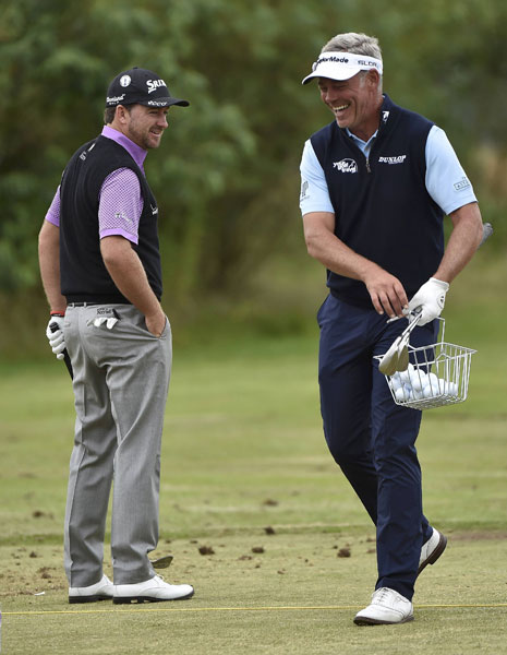 Graeme McDowell and 2011 Open champion Darren Clarke laugh on the driving range.