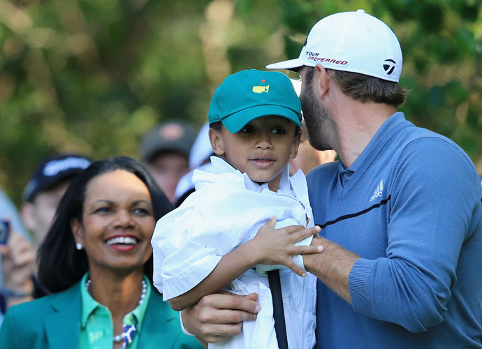 Dustin Johnson chats with former Secretary of State Condoleezza Rice during the Par 3 contest at the 2014 Masters.
