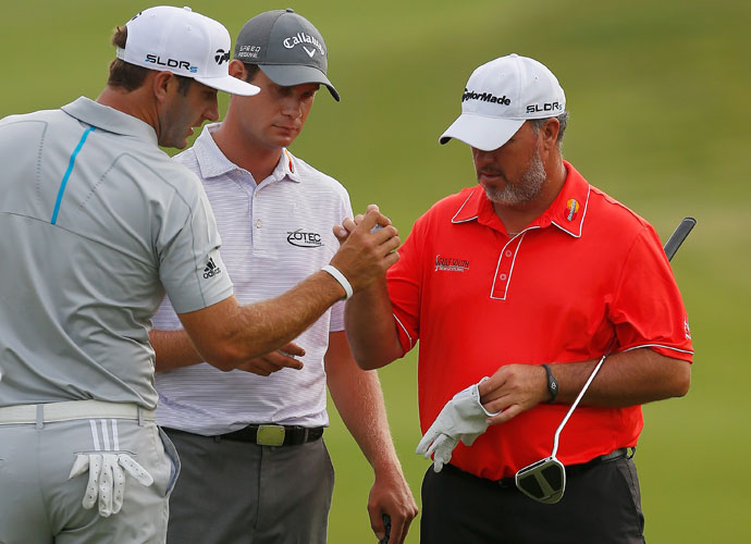 Dustin Johnson, Harris English and Boo Weekley inspect a damaged ball of Johnson's. Johnson, the first-round leader, shot 70 to stay within two shots of the lead.