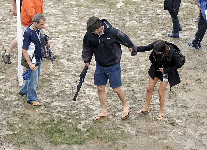 Fans trudge through the mud on a wet, sloppy day at Merion.