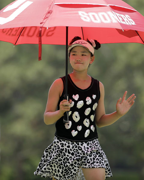 Lucy Li waves to fans as she walks down the second fairway during the second round. The 11-year-old shot her second consecutive 78 and missed the cut. She was the youngest qualifier in U.S. Open history.