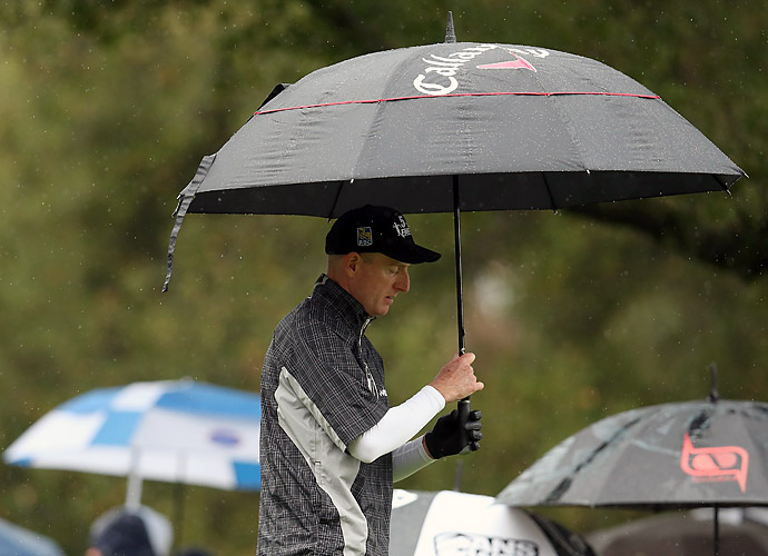 Jim Furyk grabs cover as he walks off the tee on the second hole. His 74 on Saturday dropped him to T8.