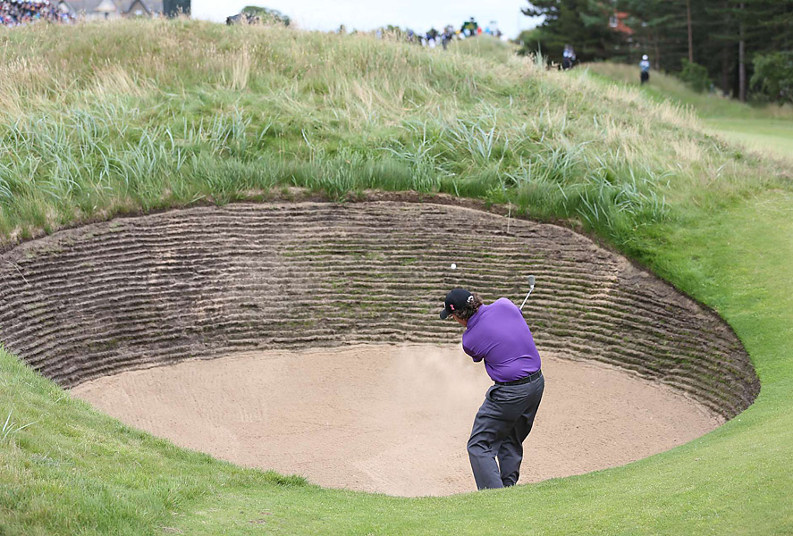 Phil Mickelson's shot from the fairway bunker on the eighth hole got stuck in the deep rough just over the lip.