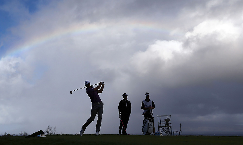 Dustin Johnson played an approach with a Hawaiian rainbow overhead. He shot a four-under 69 in Round 1.