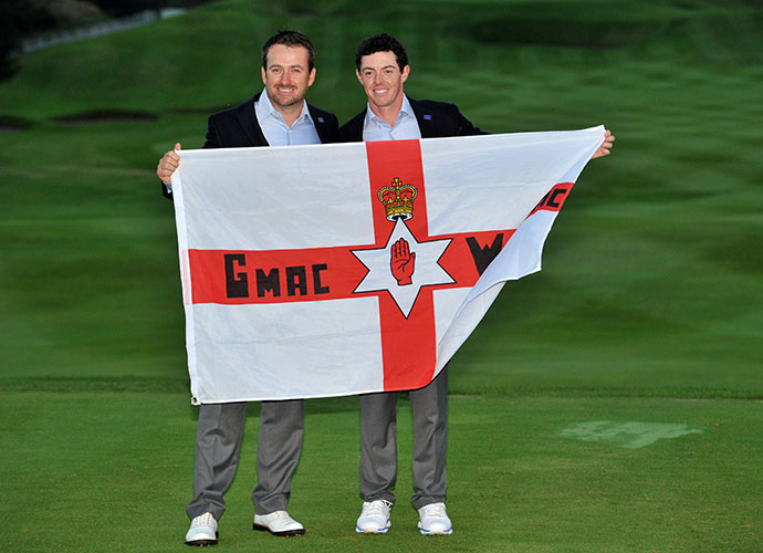 "Fellow Northern Irishmen Graeme McDowell and Rory McIlroy pose with their country's flag, adorned with ""G-Mac"" and ""Wee Mac."""